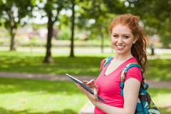 Gorgeous smiling student using tablet. On campus at college Stock Photos