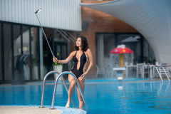 Gorgeous smiling woman in a black sexy swim suit makes selfie photo with selfie stick on resort with blurred background Stock Photos