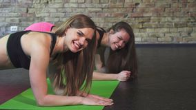 Beautiful young female friends doing planking exercise together. Gorgeous sportswoman smiling to the camera while working out with her female friend, doing stock video footage