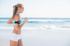Gorgeous sporty blonde in sportswear jogging. On a sunny beach royalty free stock photo