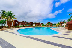 Gorgeous, stunning view of hotel grounds with cozy, comfortable swimming pool located near the beach area on sunny day Stock Images