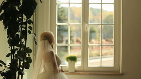 Gorgeous stylish blonde bride looking at the window and waiting for groom on the background of vintage room stock video