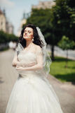 Gorgeous stylish blonde bride in vintage white dress walking in stock photography