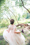 Gorgeous stylish  bride in vintage white dress walking in the park.  Beautiful wedding bride running in the forest  . Royalty Free Stock Photos