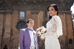 Gorgeous stylish brunette bride and groom posing near old church Royalty Free Stock Photo