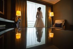 Gorgeous stylish brunette bride near a window in luxury room Royalty Free Stock Image