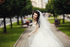 Gorgeous stylish brunette bride in vintage white dress walking in Stock Photography
