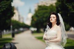 Gorgeous stylish brunette bride in vintage white dress walking in Stock Image