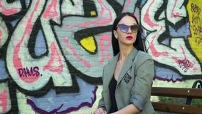 Gorgeous stylish brunette in sunglasses at background of graffiti. Stylish brunette in sunglasses and with red lipstick is posing for camera against graffiti stock video