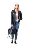 Gorgeous stylish casual woman wearing jeans and leather jacket holding black handbag. Full body length portrait isolated over white background Royalty Free Stock Photography