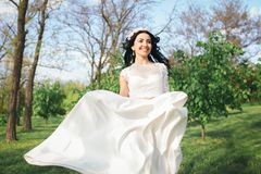Gorgeous stylish dark-haired bride in a beautiful, white dress walks in the park royalty free stock images