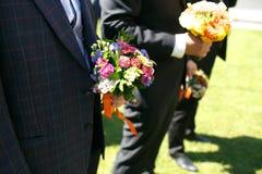 Gorgeous stylish elegant groom and best man holding colorful bou Stock Photos