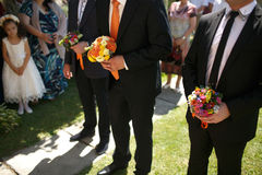 Gorgeous stylish elegant groom and best man holding colorful bou Royalty Free Stock Images