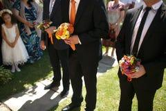 Gorgeous stylish elegant groom and best man holding colorful bou Royalty Free Stock Images