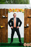 Gorgeous stylish happy groom waiting bride near wooden arch for Royalty Free Stock Images