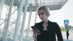 Gorgeous stylish young blonde woman in a formal outfit passing the business centre and using her phone, looks around stock footage