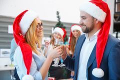 Cheerful office people in Santa caps at the Christmas party on the office background. New year concept. Gorgeous and successful business people in festive Santa Stock Image