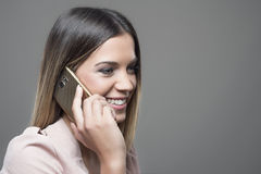 Gorgeous successful business woman talking on the mobile phone smiling. Young gorgeous successful business woman talking on the mobile phone smiling and looking Royalty Free Stock Image