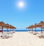 Gorgeous summer day at the beach near the sea. Beach umbrellas. Stock Photos