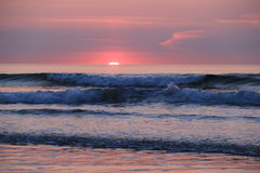 Gorgeous sunrise over the seaside horizon. Beautiful shades of pink and purple in the sunrise over seaside waves pounding to the shore Royalty Free Stock Photos