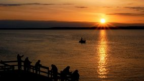 Gorgeous sunrise with sun rays over lake with silhouettes of people fishing. In boat and casting minnows and lures on pier for walleye pike stock video