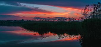 Gorgeous sunset with clouds reflected in the lake`s water stock photography