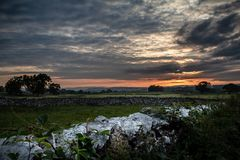 Gorgeous sunset over the fields and old dividing stones in the Lake District in Cumbria, England. UK royalty free stock images