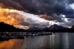 Sunset over Jackson Lake with Grand Tetons in background. Gorgeous Sunset over Jackson Lake with nautical vessels in the foreground and the Grand Tetons in the royalty free stock image