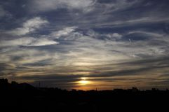 Gorgeous sunset strata cloudscape. Magical view of gorgeous sunset over cityscape stock photography