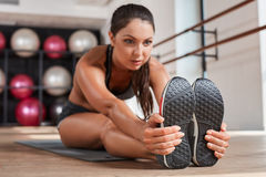 Gorgeous suntanned brunette doing exercises. A the gym. girl doing stretching on the mat Stock Photography