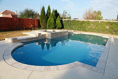Gorgeous swimming pool in lush back yard Stock Image