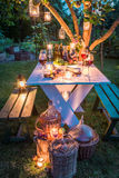 Gorgeous table with wine and candles in garden at dusk royalty free stock photos