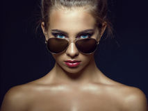 Gorgeous tanned blue-eyed model with beautiful make up and baby hair around her face looking over her trendy aviator sunglasses royalty free stock image