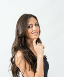Gorgeous tanned brunette beauty smiling at camera with chin leaned on her finger Royalty Free Stock Image