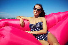 A gorgeous tanned woman posing on a pink inflatable boat on the royalty free stock photos