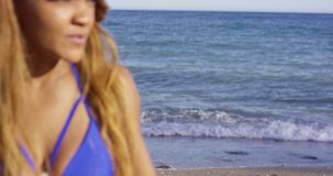 Gorgeous tanned young woman carrying her surfboard stock video