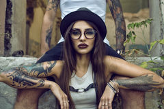 Gorgeous Tattooed Girl With Provocative Make Up Sitting Between Her Boyfriend S Legs In The Ruined Abandoned Building Stock Photos