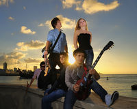 Gorgeous teen musical band posing at sunset. Portrait of young musical band with 4 boys and a girl posing outdoors at sunset with instruments, Havana skyline in Royalty Free Stock Photo