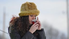 Gorgeous teen wit fur hat drinking hot tea stock footage