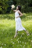Gorgeous teenage girl jumping in a flowery meadow Royalty Free Stock Image