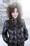 Gorgeous teenage girl with winter jacket in the city. Portrait of pretty asian teenage girl smiling at the camera while wearing winter jacket with furry hood in Royalty Free Stock Images