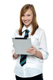 Gorgeous teenager browsing on her tablet pc Stock Photography