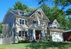 Gorgeous Upscale Home in Dappled Sunlight. Gorgeous home sitting on a hill with bright green shrubs, red door, and stone and vinyl siding stock photos