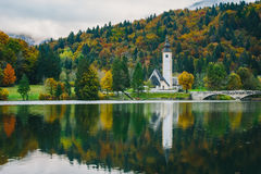 Gorgeous view of colorful autumnal scene of famous Church of St John the Baptist, Bohinj Lake, Ribicev Laz, touristic village in S Royalty Free Stock Photography
