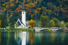 Gorgeous view of colorful autumnal scene of famous Church of St John the Baptist, Bohinj Lake, Ribicev Laz, touristic village in S Stock Photo