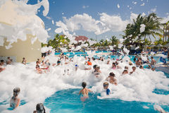 Gorgeous view of happy smiling joyful people relaxing and enjoying their time in swimming pool foam party on sunny day Royalty Free Stock Image