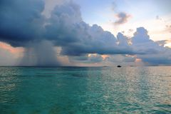 Gorgeous view of Indian Ocean, Maldives. Lonely fishing boat on beautiful turquoise water surface far away. Huge white clouds and heavy rainfall on a distance stock image