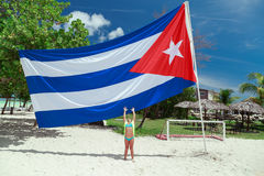 Gorgeous view of a little girl on tropical beach stretching her arms to Cuban flag Stock Image
