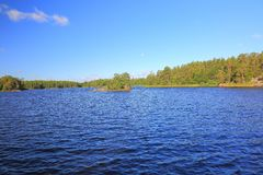 Gorgeous view of natural landscape. Wide lake with green pine trees on coast line. Blue sky with few white clouds. Sweden, Europe. Beautiful backgrounds stock photography