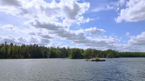 Gorgeous view of natural landscape. Wide lake with green pine trees on coast line. Blue sky with few white clouds.